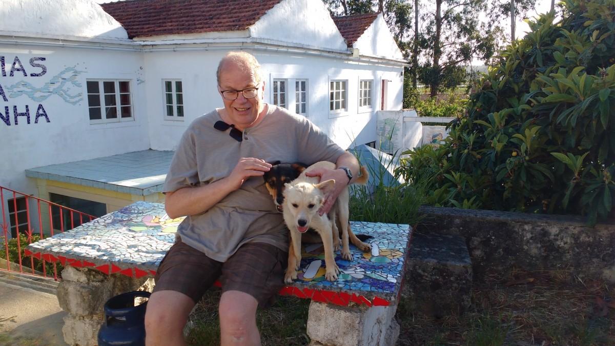 een-man-met-twee-hondjes-zittend-op-een-tafel