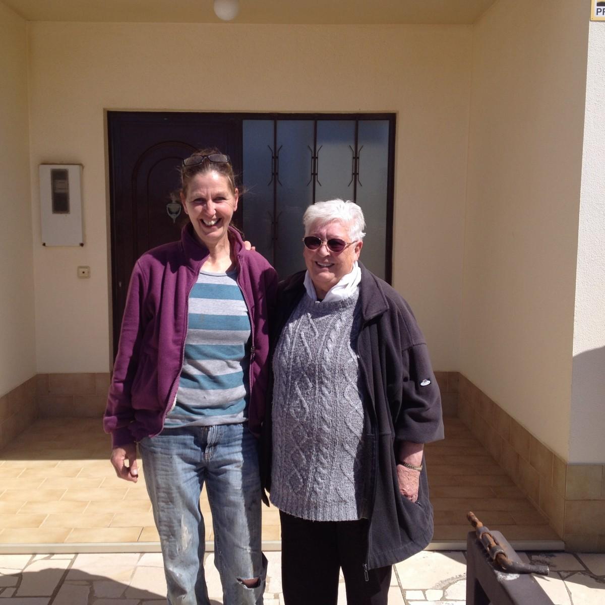 een-middelbare-en-een-oudere-vrouw-voor-een-huis