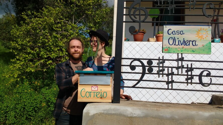 Padephanie-the couple of goldsmiths standing in front of their DIY mailbox of Casa Oliveira, Termas-da-Azenha