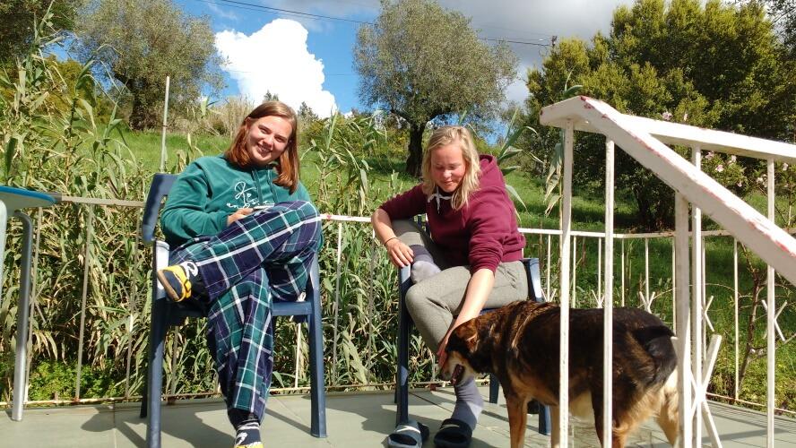 the two students sit on their veranda enjoying the sun