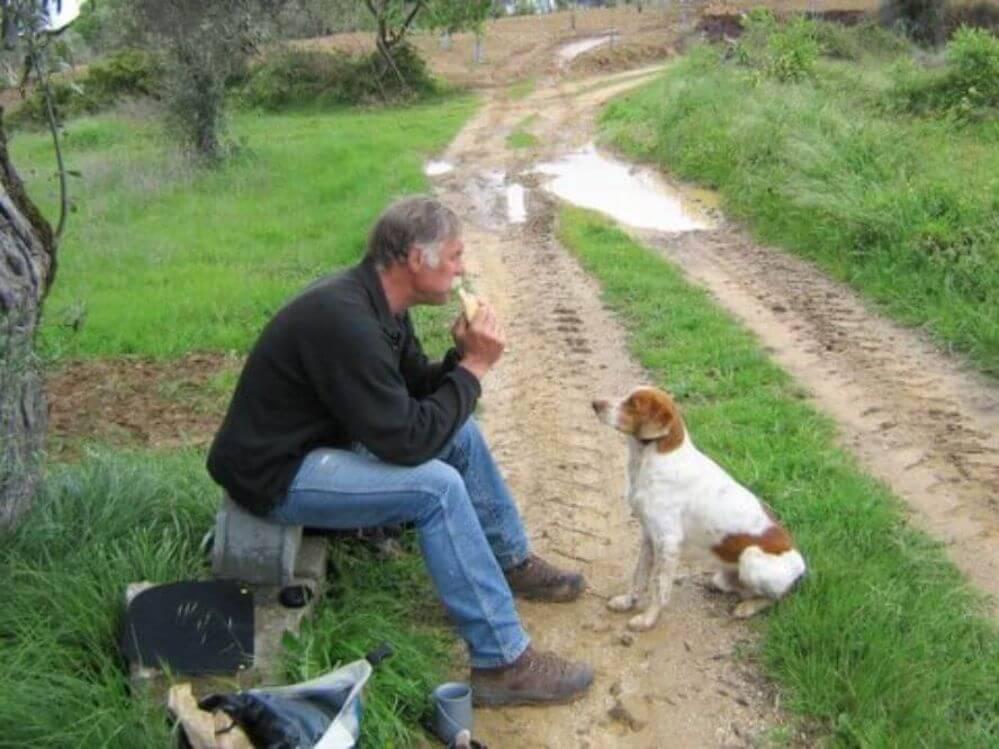 um-homem-e-um-cao-almoçar-durante-um-passeio