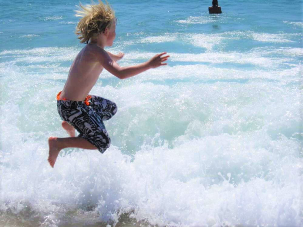 a-boy-jumps-into-the-waves